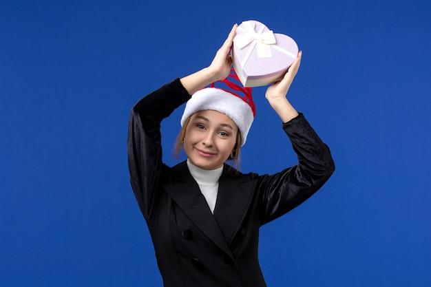 Giovane signora di vista frontale con presente a forma di cuore sul regalo di festa del nuovo anno della parete blu