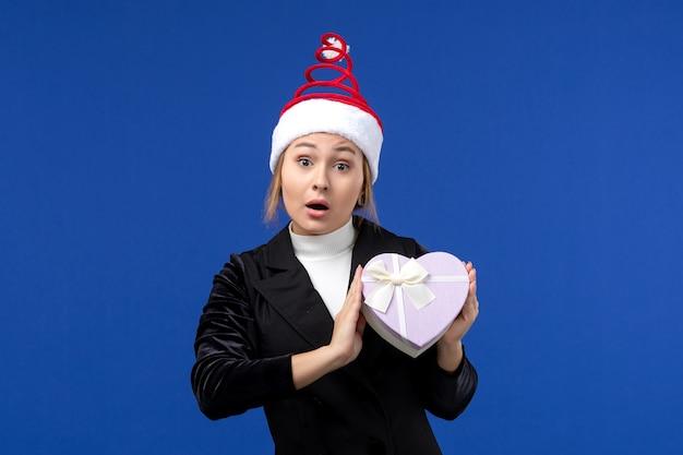 Giovane signora di vista frontale con il presente a forma di cuore sul regalo di feste di capodanno della parete blu