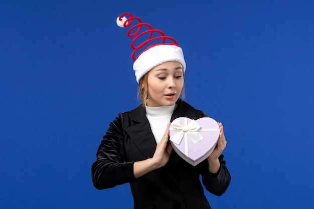 Вид спереди юная леди с подарком в форме сердца на синей стене новогодние праздничные подарки