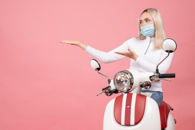 오토바이 근처에 왼쪽 서에서 가리키는 마스크와 전면보기 젊은 아가씨