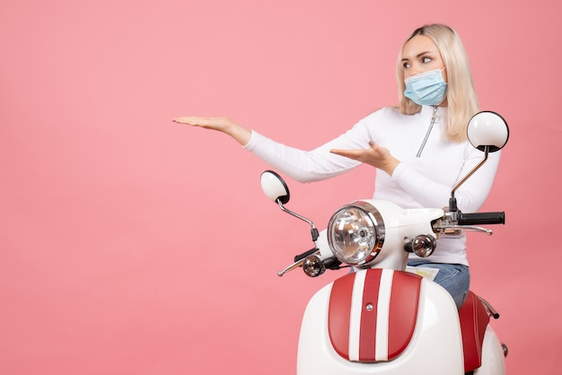 Front view young lady with mask pointing at left standing near moped