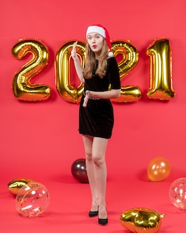 Front view young lady with santa hat balloons on red