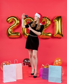 Front view young lady with santa hat holding card bags on floor balloons on red