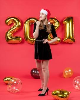 Vista frontale giovane donna con cappello da babbo natale che mette la mano su palloncini in vita su rosso