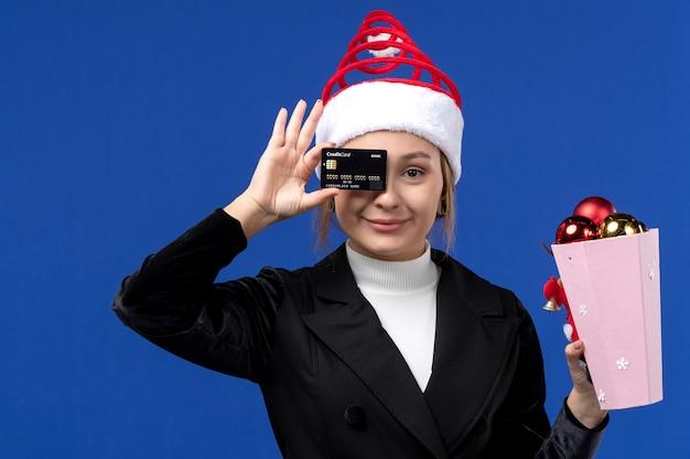 Giovane signora di vista frontale con i giocattoli dell'albero e la carta di credito sulla vacanza di emozione del nuovo anno della parete blu