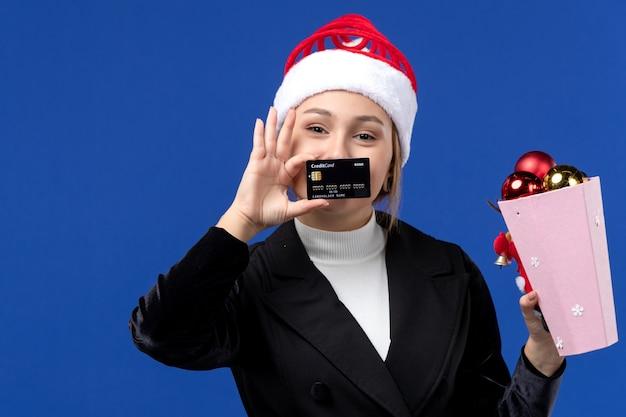 Giovane signora di vista frontale con i giocattoli dell'albero e la carta di credito sulla vacanza di emozioni del nuovo anno della parete blu