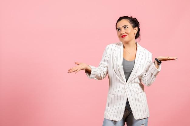 Vista frontale giovane donna con giacca bianca su sfondo rosa donna emozioni moda sensazione colore donna