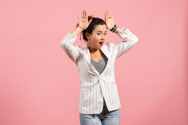 Vista frontale giovane donna con giacca bianca in posa su uno sfondo rosa chiaro moda donna emozione colore sensazione lady