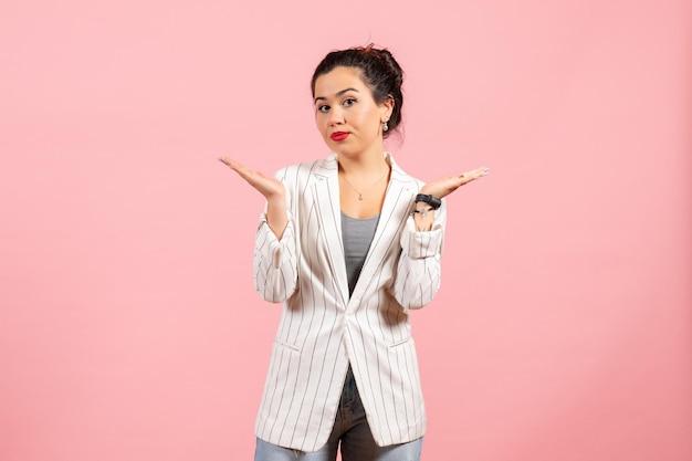 Vista frontale giovane donna con giacca bianca in posa su sfondo rosa moda donna emozione colore sensazione lady