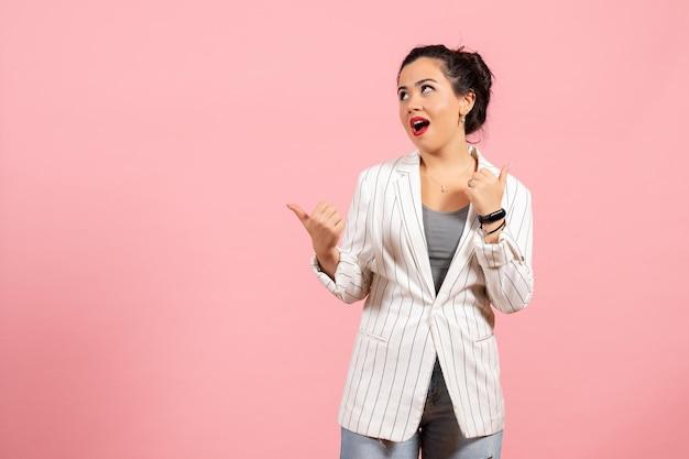 Vista frontale giovane donna con giacca bianca in posa sullo sfondo rosa moda donna emozioni colore sensazione lady