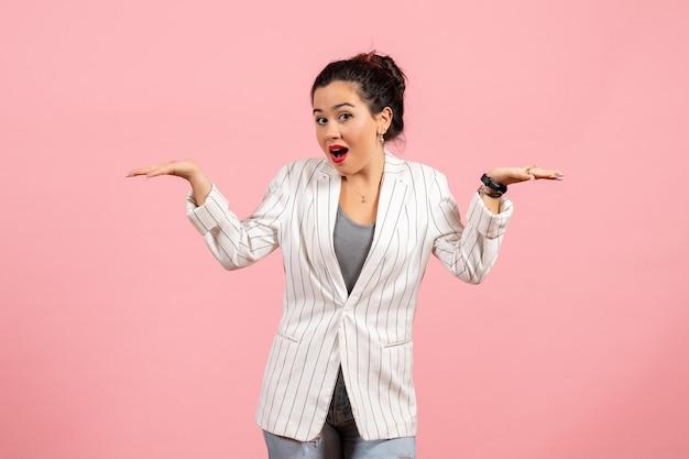 Vista frontale giovane donna con giacca bianca in posa su sfondo rosa sensazione signora emozione moda donna colore