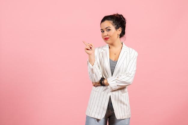 Vista frontale giovane donna con giacca bianca in posa su sfondo rosa sensazione donna emozioni moda donna colore