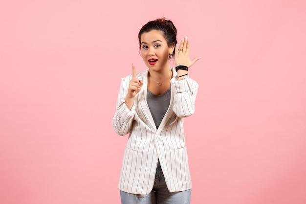 Vista frontale giovane donna con giacca bianca in posa su sfondo rosa emozioni donna moda donna colore sentimento