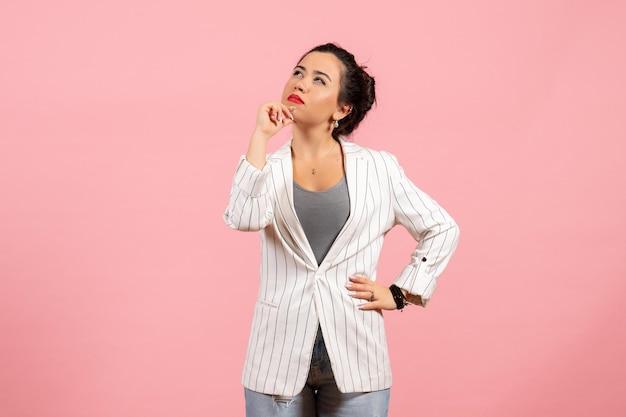 Vista frontale giovane donna con giacca bianca in posa e pensando su sfondo rosa emozioni donna moda donna colore sentimento
