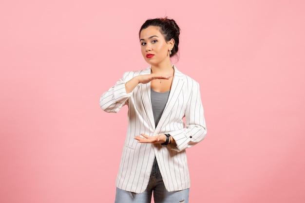Vista frontale giovane donna con giacca bianca che mostra le dimensioni su sfondo rosa emozioni donna moda sensazione colore donna