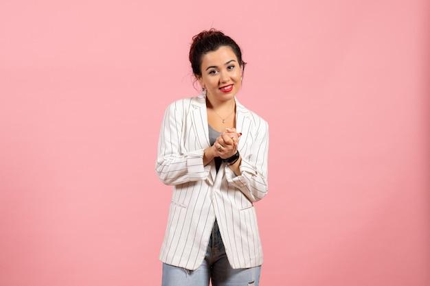Vista frontale giovane donna con giacca bianca sorridente su sfondo rosa moda donna emozione colore sensazione lady