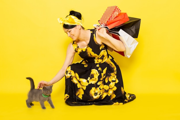 A front view young lady in yellow-black flower designed dress with yellow bandage on head holding shopping packages caressing cat on the yellow