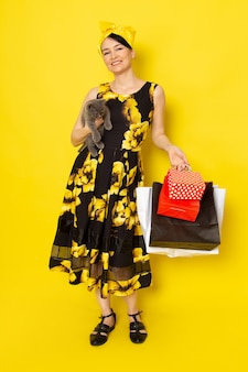 A front view young lady in yellow-black flower designed dress with yellow bandage on head holding shopping packages and kitten on the yellow