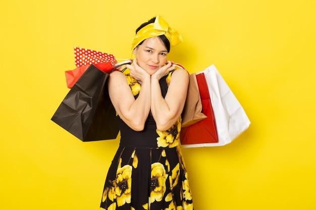 Una giovane donna vista frontale in abito giallo-nero progettato con fasciatura gialla sulla testa tenendo i pacchetti commerciali sul giallo