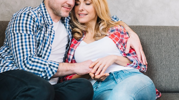 Front view of young loving couple sitting on couch