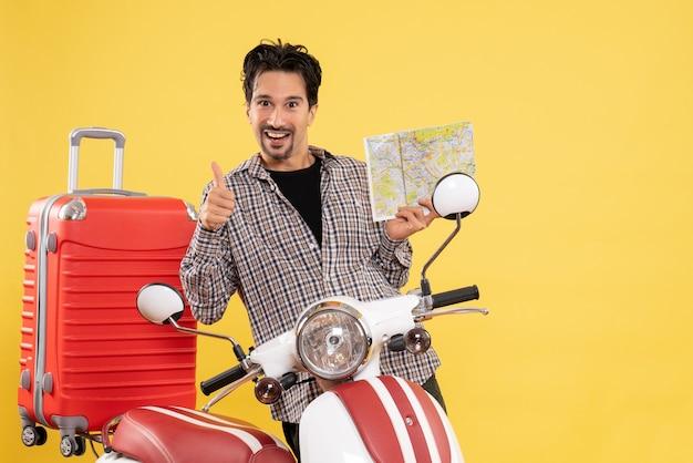 黄色の背景にロードトリップ休暇に乗るバイクの航海に地図を保持している自転車の周りの若い男性の正面図