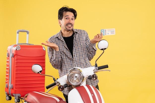 黄色の背景に道路旅行の休暇のオートバイの航海に飛行機のチケットを保持している自転車の周りの若い男性の正面図