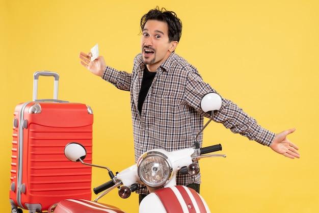 Vista frontale giovane maschio intorno alla bici che tiene il biglietto aereo su uno sfondo giallo viaggio su strada vacanza giro in moto viaggio