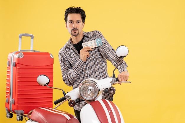 Vista frontale giovane maschio intorno alla bici che tiene il biglietto su sfondo giallo viaggio in moto viaggio in moto