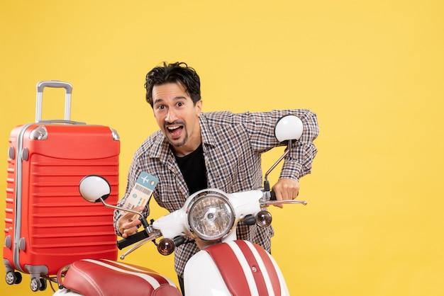 Vista frontale giovane maschio intorno alla bici che tiene il biglietto su sfondo giallo viaggio vacanza giro in moto voyage