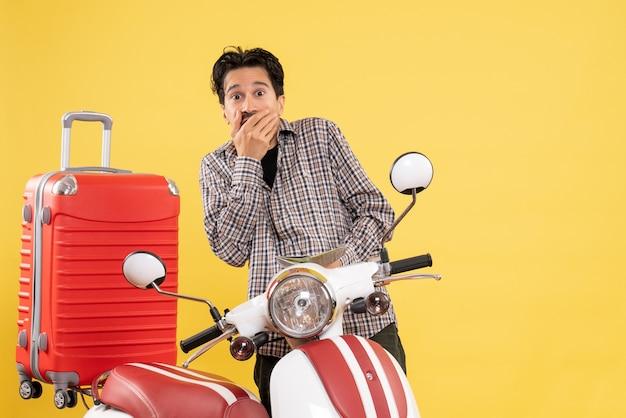 Vista frontale giovane maschio intorno alla bici osservando la mappa su sfondo giallo viaggio su strada vacanza in motocicletta