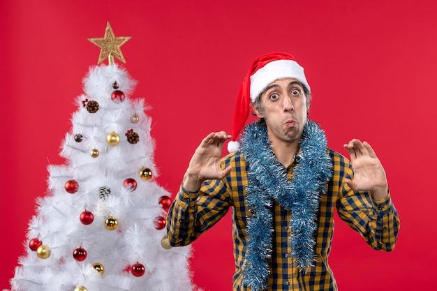 Вид спереди молодого мужчины вокруг новогодней атмосферы на красной стене в праздничных рождественских цветах