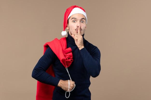 Вид спереди молодой самец просит молчать на коричневом фоне рождественских праздников санта