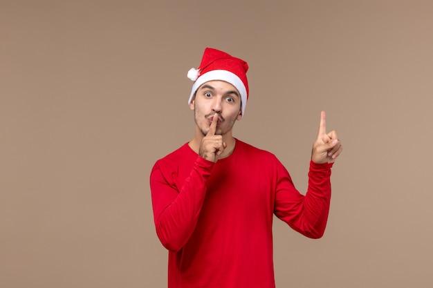 Вид спереди молодой самец просит молчать на коричневом фоне рождественские эмоции праздник самца