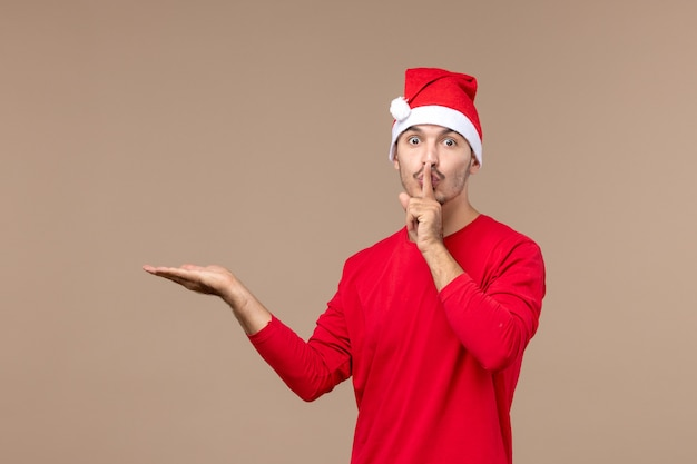 Вид спереди молодого мужчины, просящего молчать на коричневом столе, рождественский праздник эмоций