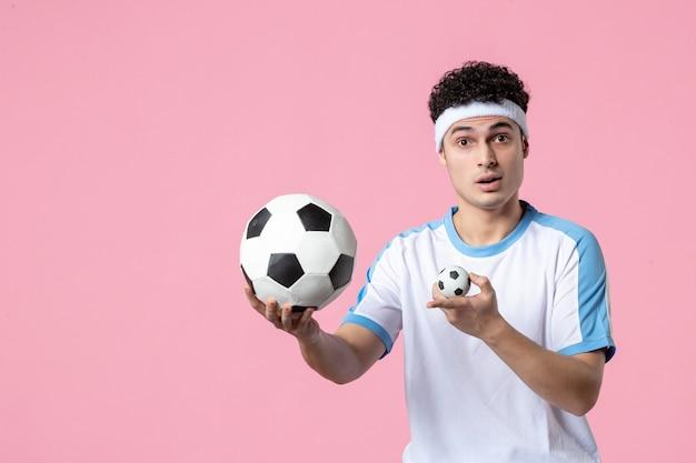 ピンクの壁にサッカーボールとスポーツ服を着た若い男性アスリートの正面図