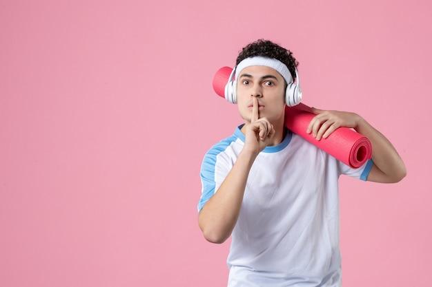 ピンクの壁にヨガマットとスポーツ服を着た若い男性アスリートの正面図