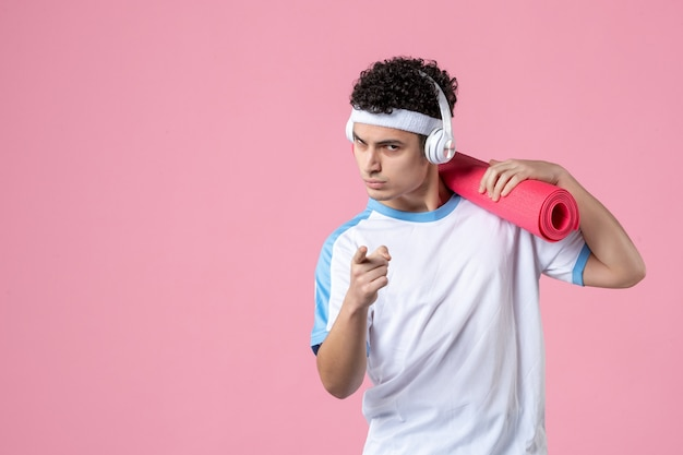 Vista frontale giovane atleta maschio in abiti sportivi con materassino yoga sulla parete rosa