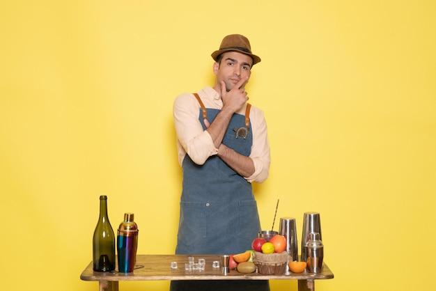 Vista frontale giovane barista maschio davanti al tavolo con agitatori e bevande pensando su sfondo giallo