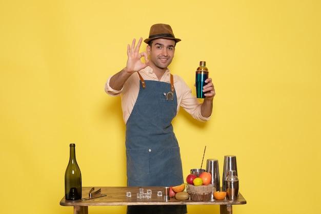 Вид спереди молодой мужчина-бармен перед столом с напитками, держа шейкер на желтом фоне