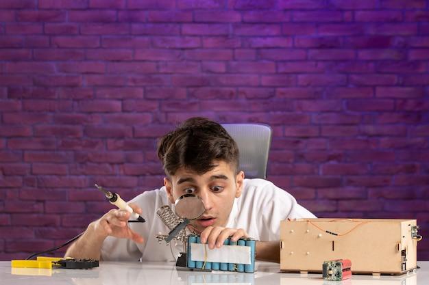 보라색 벽에 작은 집 레이아웃을 수정하려고 책상 뒤에 전면보기 젊은 남성