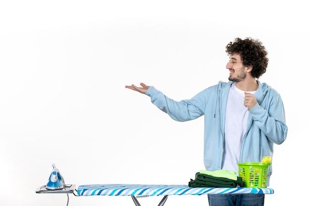 정면도 젊은 남성 흰색 바탕에 다림판 뒤에 있는 남자 청소 집안일 세탁 사진 철 옷