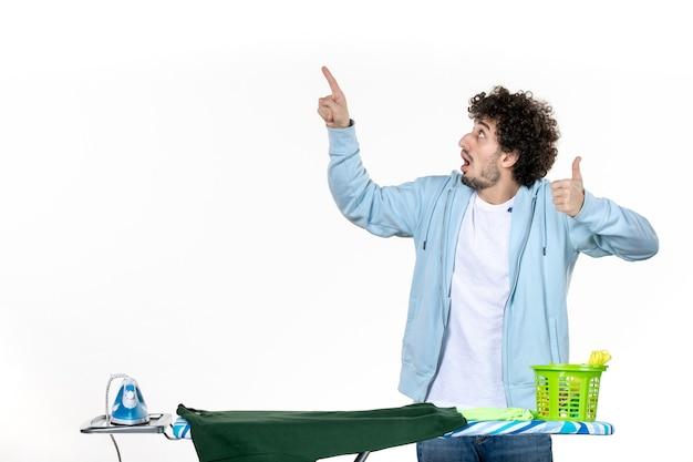 전면보기 젊은 남성 흰색 배경에 다림판 뒤에있는 집안일 다림질 세탁 청소 감정 남자 색상