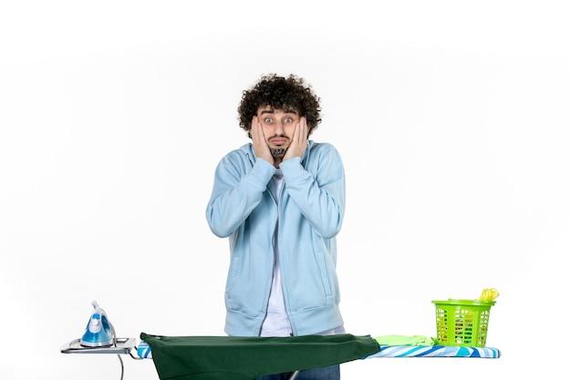 전면보기 젊은 남성 흰색 배경에 다리미판 뒤에 세탁 가사 감정 색깔 인간의 청소 옷