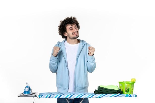 흰색 배경에 웃는 다림판 뒤에 젊은 남성 전면보기 집안일 세탁 청소 옷 사진 철 색상