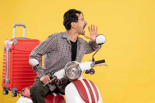 Giovane maschio di vista frontale sulla bici con la sua borsa che chiama ad alta voce qualcuno sul giallo