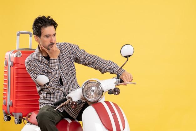 Giovane maschio di vista frontale sulla bici con la sua borsa che pensa sul giallo