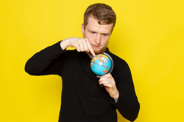 Front view of young male in black shirt holding little globe