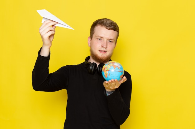 Front view of young male in black shirt holding paper plane and little globe