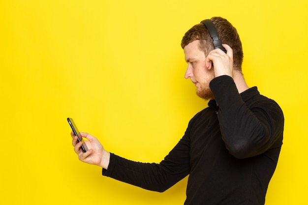 Front view of young male in black shirt listening to music via earphones