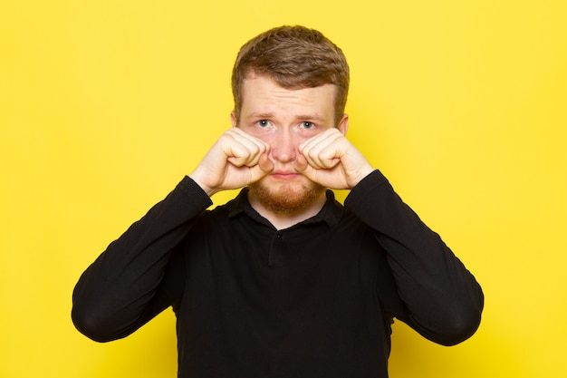 Front view of young male in black shirt posing and fake crying